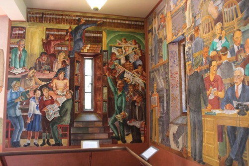 Coit Tower murals depicting the newspaper office on the one wall and the readers on the other wall.